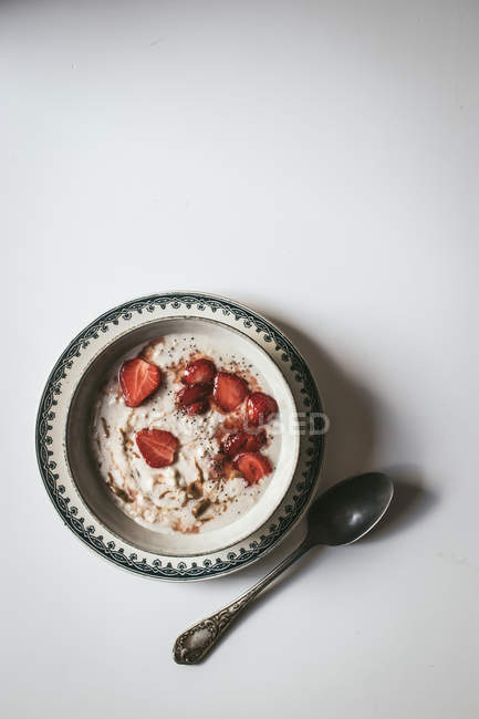 Served oatmeal in bowl with strawberries and chia seeds in white background — Stock Photo
