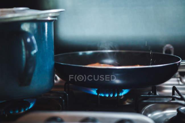 На кухне подожгли большую металлическую кружку и сковородку — стоковое фото