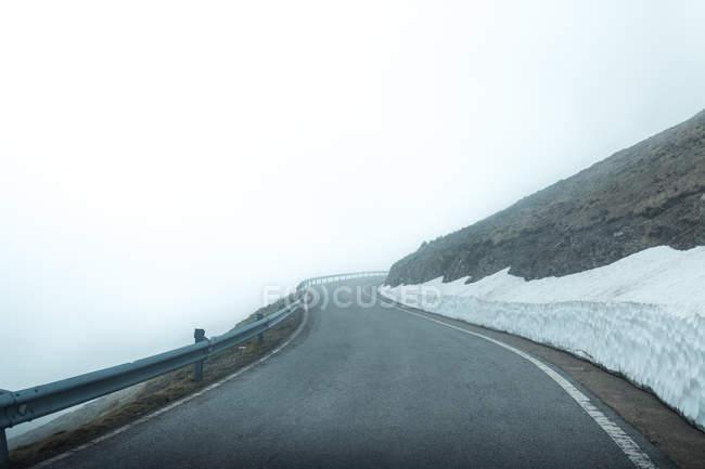 Asphalt road through snowy mountainous terrain on misty day — Stock Photo