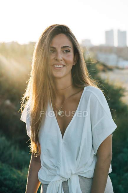 Jovem sorrindo mulher em roupas brancas olhando para longe na luz do sol — Fotografia de Stock