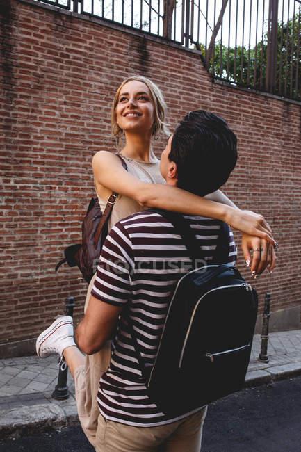 Seitenansicht des jungen fröhlichen Paares, das Spaß beim Dating im Freien hat — Stockfoto