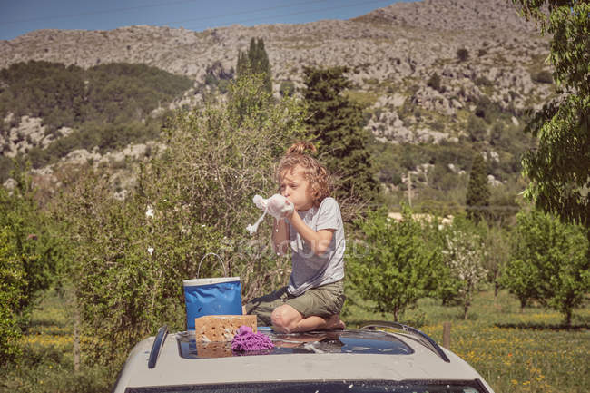 Adorable happy energetic child with cleaning tools playing with foam sitting on foamy glass roof of car while washing — Stock Photo