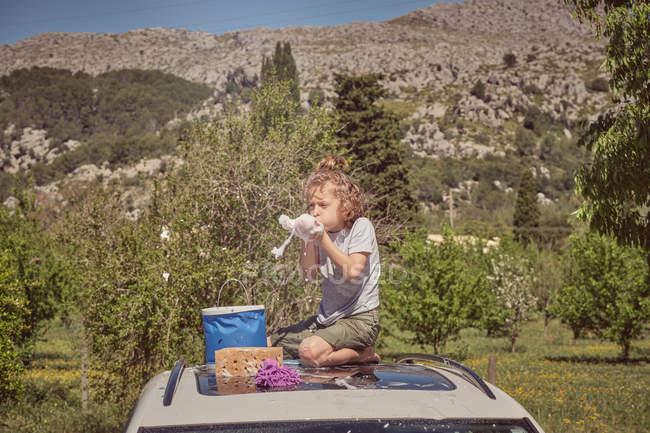 Adorabile bambino energico felice con strumenti di pulizia giocando con schiuma seduta sul tetto di vetro schiumoso dell'auto durante il lavaggio — Foto stock