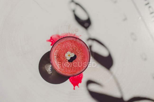 Пузырь пенный вкусный ароматный розовый смузи украшен цветком в стекле на белой поверхности с тенью — стоковое фото