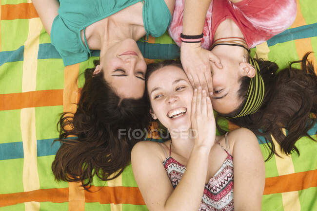 From above young teenage women in bright clothes having fun and making faces while lying down on colorful plaid — Stock Photo