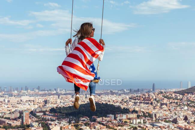 Junges Mädchen feiert den 4. Juli mit der amerikanischen Flagge auf einer Schaukel — Stockfoto
