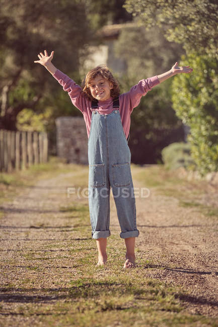 Gioioso bambino scalzo in piedi sulla strada di campagna e alzando le mani — Foto stock