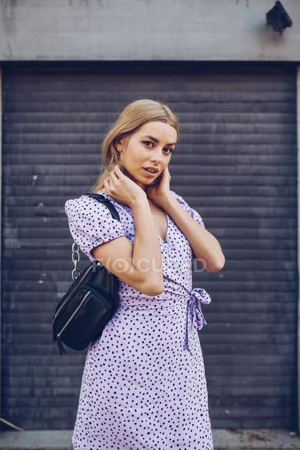 Retrato de mujer joven atractiva en vestido de pie en la calle y mirando en la cámara - foto de stock