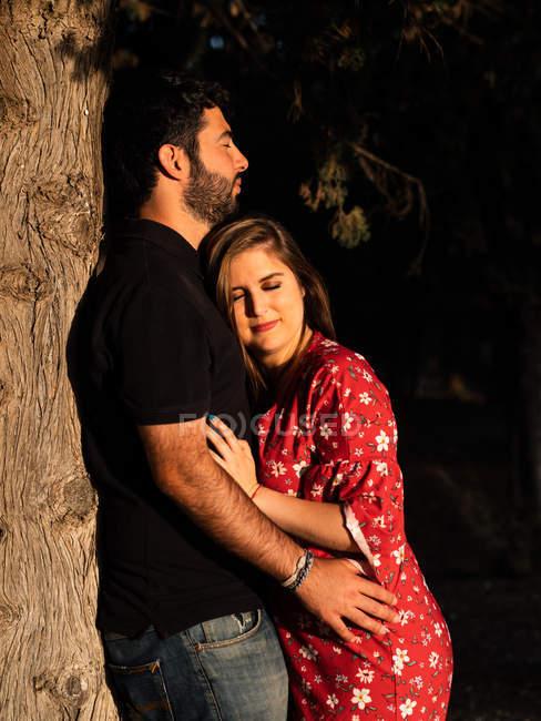 Hombre abrazando sonriendo esposa embarazada en el fondo de la naturaleza - foto de stock