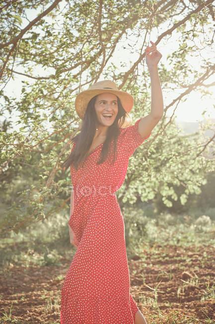Молодая привлекательная веселая женщина в красном платье танцует и улыбается в зеленом саду в летний день — стоковое фото