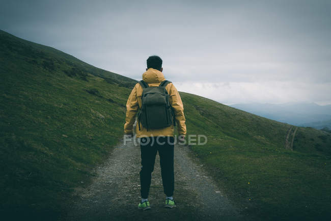 Back view of unrecognizable male with backpack standing on rough path on grassy hill slope against gray overcast sky in nature — Stock Photo