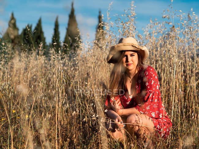 Привлекательная улыбающаяся женщина в соломенной шляпе и красном платье сидит на диком поле на фоне голубого неба — стоковое фото