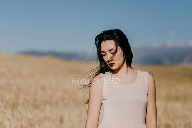 Hermosa hembra asiática mirando hacia abajo mientras está de pie sobre el fondo borroso del prado en el día ventoso en la naturaleza - foto de stock