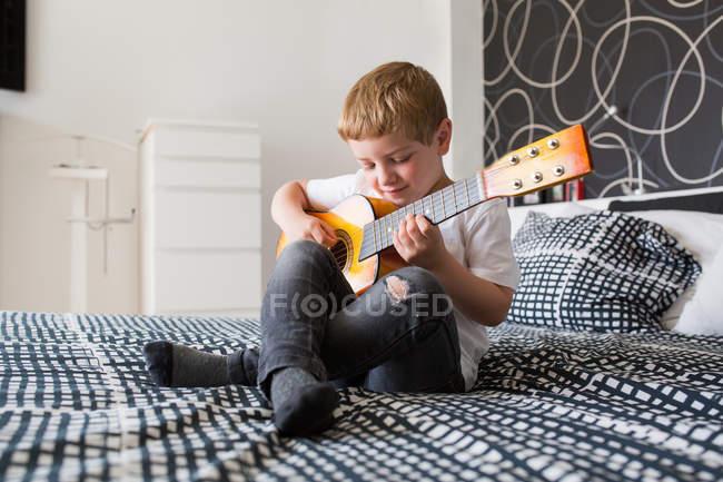 Молодой блондин играет на игрушечной гитаре — стоковое фото