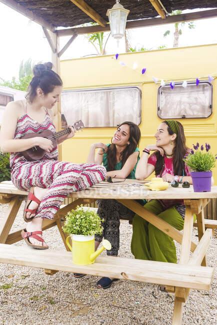Giovane donna attraente giocare ukulele seduto sul tavolo con fidanzate godendo la musica in cortile contro van — Foto stock
