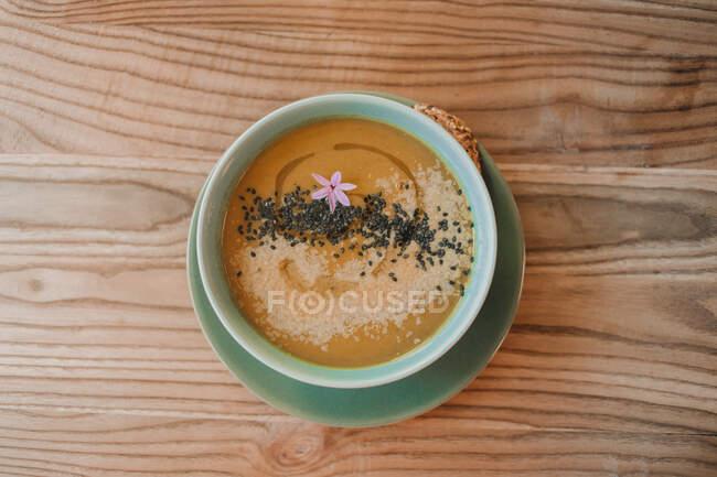 Пюре из жёлтого супа с чёрными семенами в голубой миске и овсяным хлебом на тарелке — стоковое фото