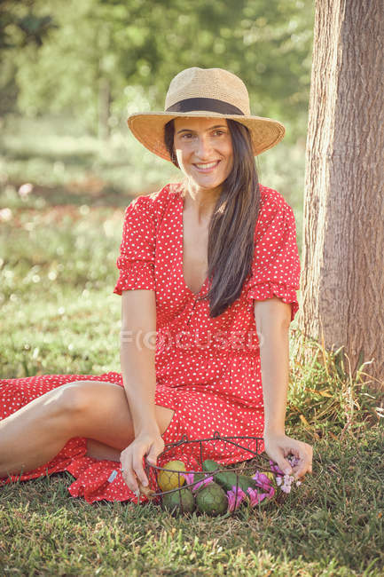 Young attractive woman in hat and red dress with basket of fruits and flowers sitting on grass in green garden in summer day — Stock Photo