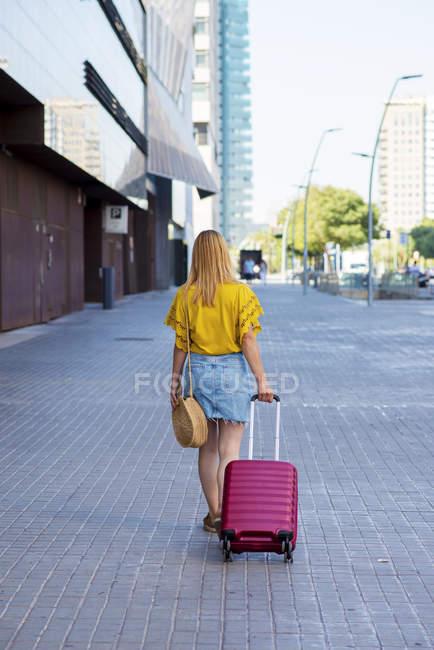 Vista posteriore di giovane turista femminile con valigia a piedi sulla strada — Foto stock