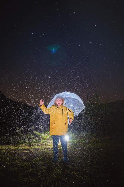 Ребенок в желтой куртке стоит под белым зонтиком и звезды в темноте ночи — стоковое фото