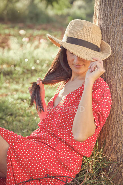 Frau in rotem Kleid mit Hut sitzt im grünen Garten an einem Sommertag — Stockfoto