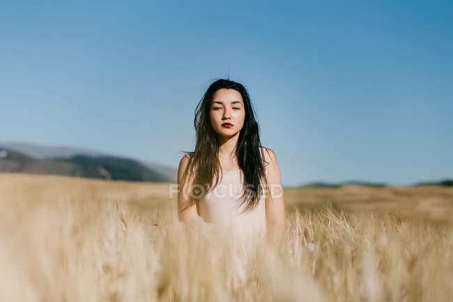 Beautiful Asian female looking at camera while standing on blurred background of meadow on windy day in nature — Stock Photo