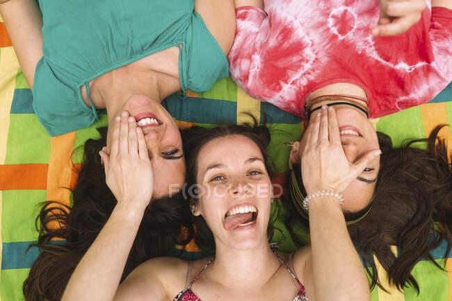 De cima jovens mulheres adolescentes em roupas brilhantes se divertindo e fazendo rostos enquanto deitado em xadrez colorido — Fotografia de Stock