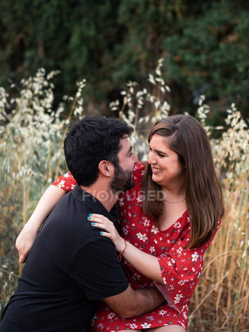 Man hugging smiling pregnant wife sitting on lap on background of picturesque green park — Stock Photo