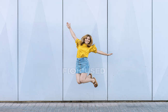 Young cheerful woman jumping in air on blue background — Stock Photo