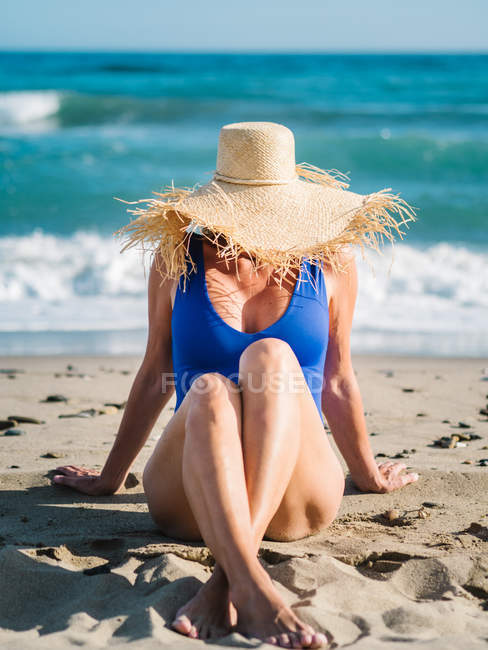 Slim tanned woman in blue swimsuit and hat hiding face and sitting with crossed legs on sandy beach in bright day — Stock Photo