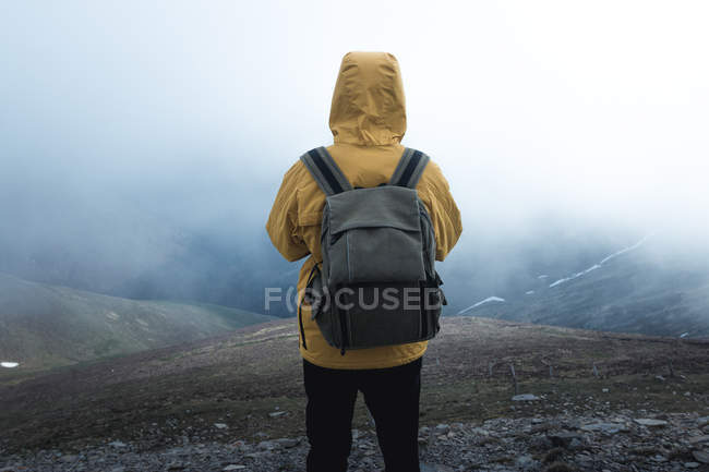 Back view of guy with backpack standing on hillside against thick fog during trip in nature — Stock Photo