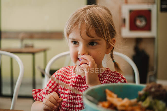 Appetizing fragrant assorted food in blue bowl and adorable girl eating at table — Stock Photo