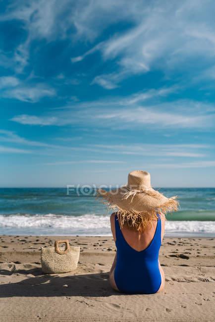 Opinião traseira a mulher bonita no chapéu e no Swimsuit que sentam-se com o saco no beira mar arenoso que olha ondas o céu nebuloso de turquesa — Fotografia de Stock