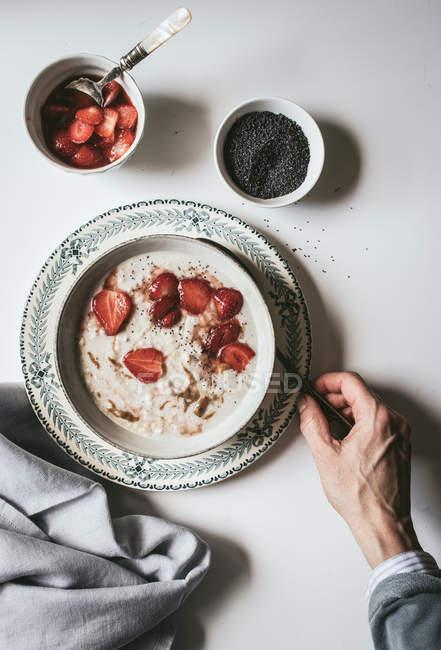 Рука людини виступає вівсянки в миску з полуницею і насіння чіа в білому фоні — стокове фото