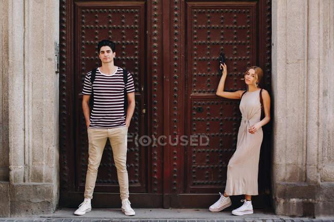 Joven pareja alegre y juguetona en ropa casual posando frente a la hermosa puerta vieja - foto de stock