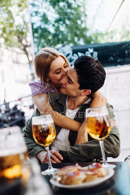 Cheerful young attractive woman kissing man while enjoying refreshing drink — Stock Photo