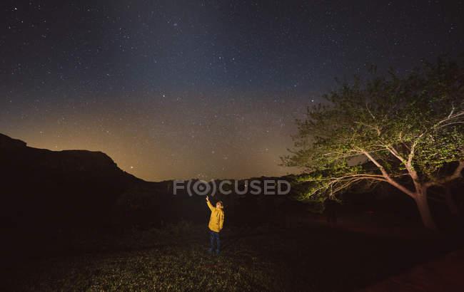 Хлопчик у жовтій куртці стоїть під зорями в темну ніч, вказуючи на небо. — стокове фото