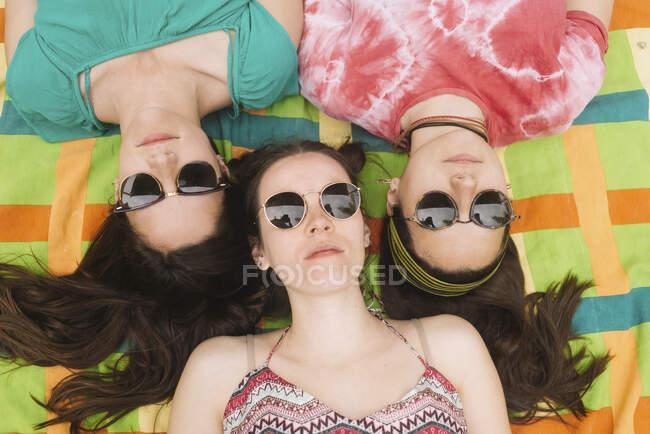 D'en haut trois jeunes femmes attirantes en vêtements brillants s'amusant à faire des grimaces dans des lunettes de soleil noires couchées dans une couverture colorée — Photo de stock