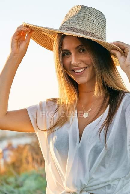 Jovem mulher em roupas brancas e chapéu de palha elegante sorrindo e olhando para a câmera na natureza — Fotografia de Stock