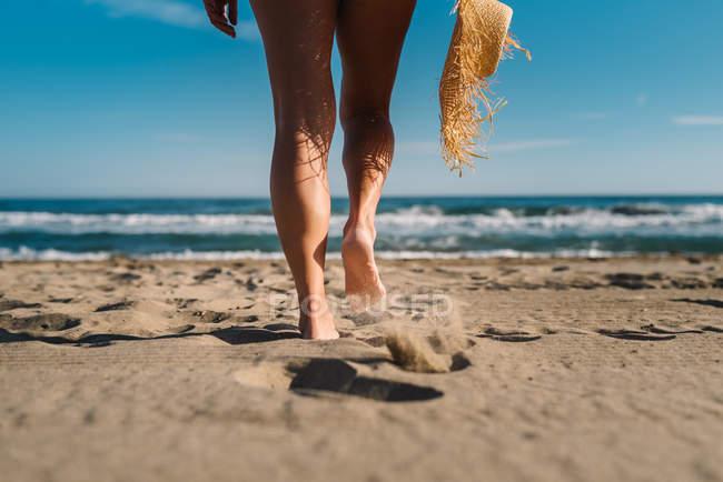 Вид сзади на женские обрезанные ноги в соломенной шляпе на побережье при ярком солнечном свете — стоковое фото