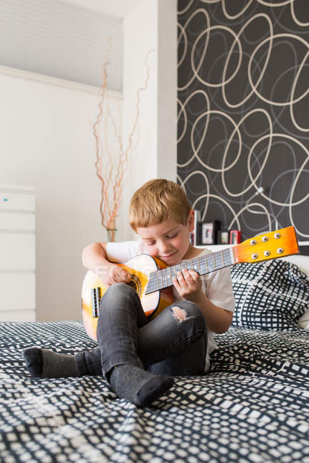 Young blonde boy playing toy guitar — Stock Photo