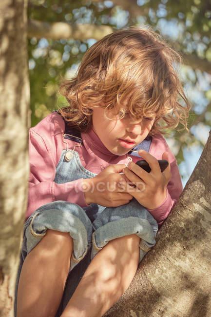 Enfant mignon réfléchi grimpant arbre et passer du temps avec téléphone mobile dans la journée lumineuse — Photo de stock