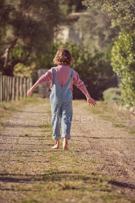 Vista posteriore di gioioso bambino scalzo in piedi sulla strada di campagna e alzando le mani — Foto stock