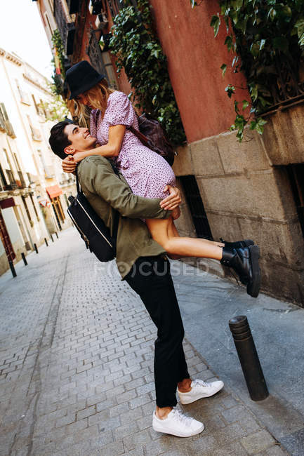 Cheerful young man having fun and carrying girlfriend during city date — Stock Photo
