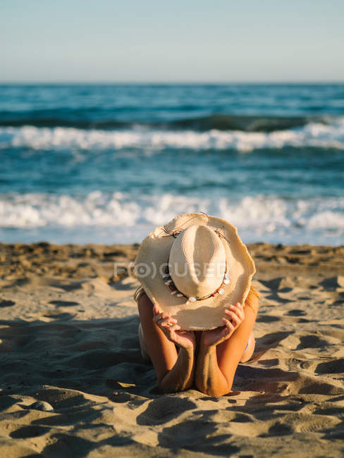 Tanned unrecognizable woman in hat lying sunbathing on sandy seaside in sunny day — Stock Photo