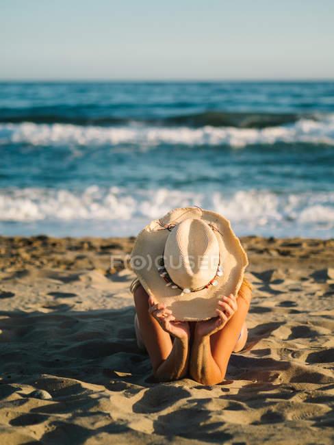 Загорелая неузнаваемая женщина в шляпе загорает на песчаном побережье в солнечный день — стоковое фото
