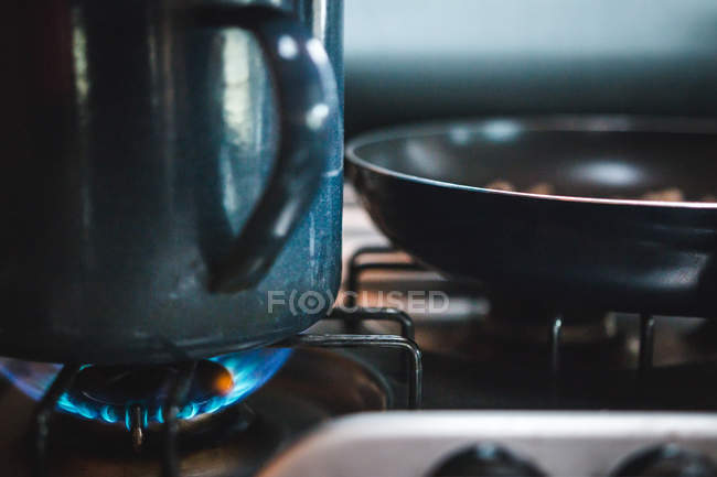 Encerramento caneca de metal grande e frigideira colocada no fogo do fogão a gás na cozinha — Fotografia de Stock