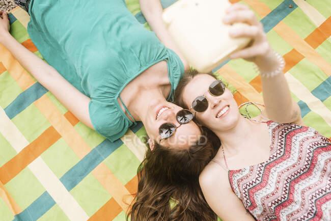 Сверху молодые привлекательные женщины лежат вместе на красочном одеяле и делают селфи с мгновенной фотокамерой — стоковое фото