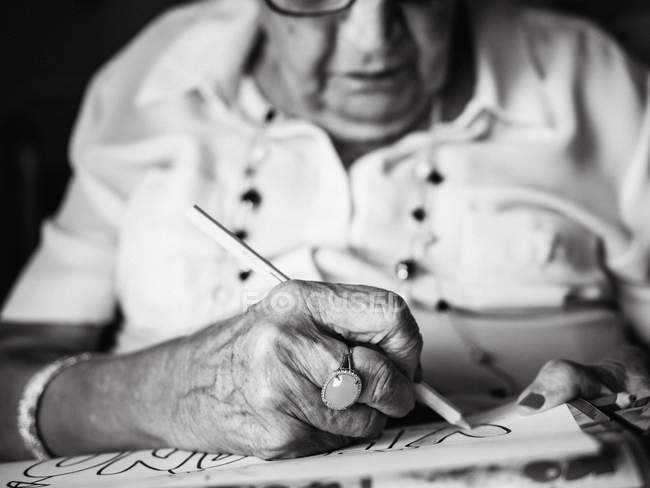 Senior woman in white shirt and glasses drawing on paper with pencil sitting on armchair at home — Stock Photo