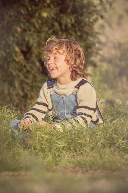 Adorable niño serio en overoles de mezclilla sentado en hierba verde y mirando hacia otro lado en un día soleado - foto de stock