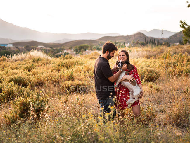 Smiling cheerful couple having fun and holding little dog among high grass in countryside — Stock Photo